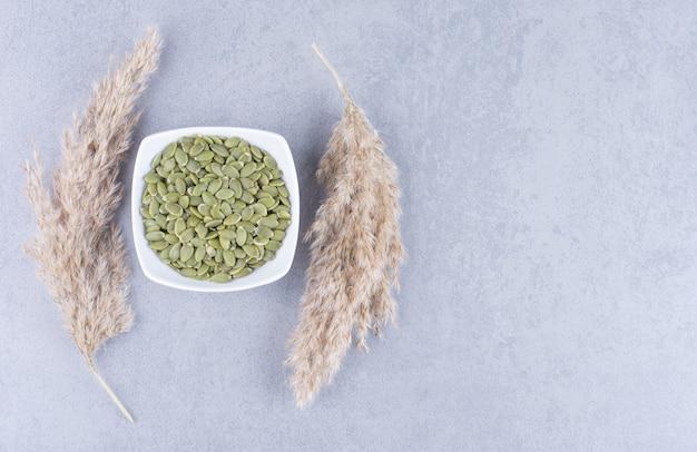 Тыквенные семечки в миске рядом с пампасной травой, на мраморе.