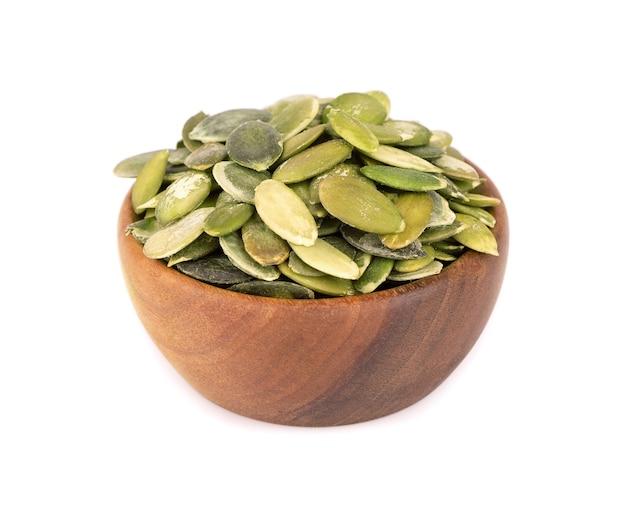 흰색 배경에 고립 된 나무 그릇에 호박 씨앗. 녹색 pepita 씨앗.