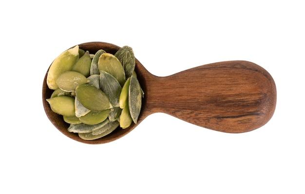 Семена тыквы в деревянной ложке, изолированные на белом фоне. семена зеленой пепиты. вид сверху.