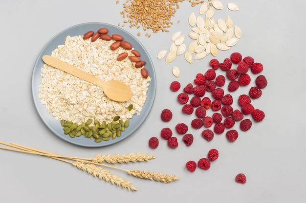 灰色のボウルにカボチャの種、ナッツ、オートミール。テーブルの上の小麦の小穂とラズベリー。フラットレイ。灰色の背景