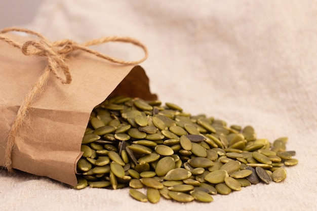 Pumpkin seeds in a paper bag on natural linen. pumpkin seeds vitamins of group b and magnesium.