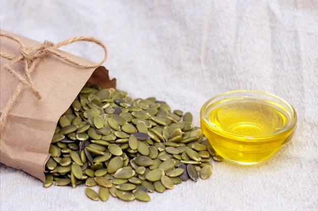 Pumpkin seeds in a paper bag, pumpkin seed oil on natural linen. pumpkin seeds vitamins of group b and magnesium.