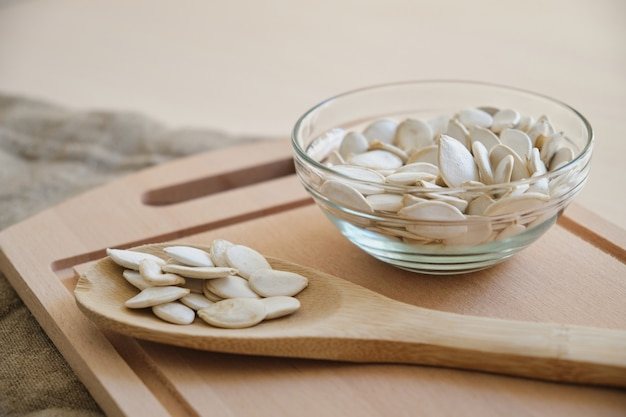 Pumpkin seeds in white bowl and spoon on the flax on the table copy space