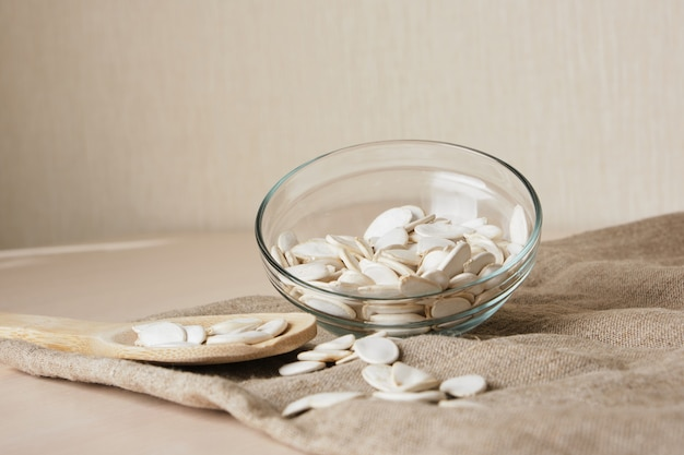 Pumpkin seeds in white bowl and spoon on the flax on the table
