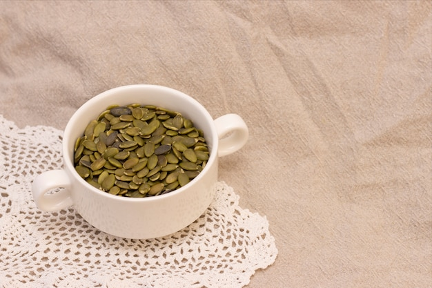 Pumpkin seeds, in a white cup on natural linen. pumpkin seeds vitamins of group b and magnesium.