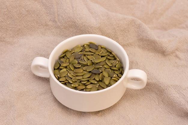 Pumpkin seeds, in a white cup on natural linen. pumpkin seeds vitamins of group b