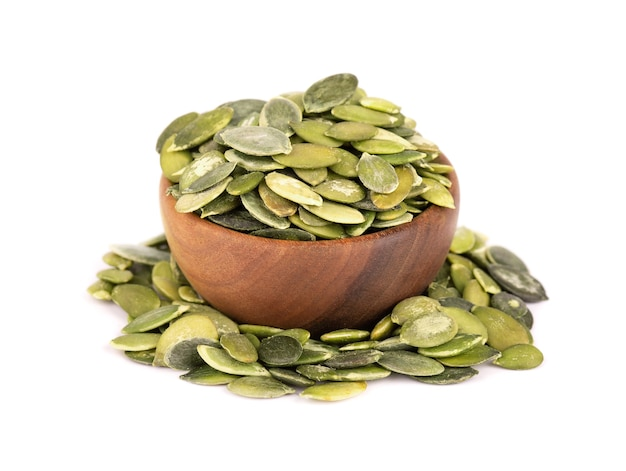 Pumpkin seeds in wooden bowl, isolated on white background.