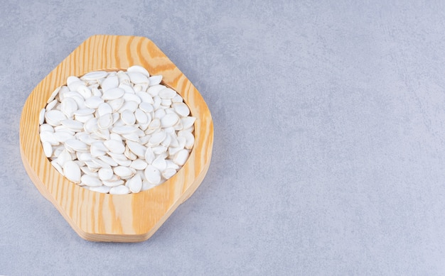 Pumpkin seeds in a wooden plate on the marble surface