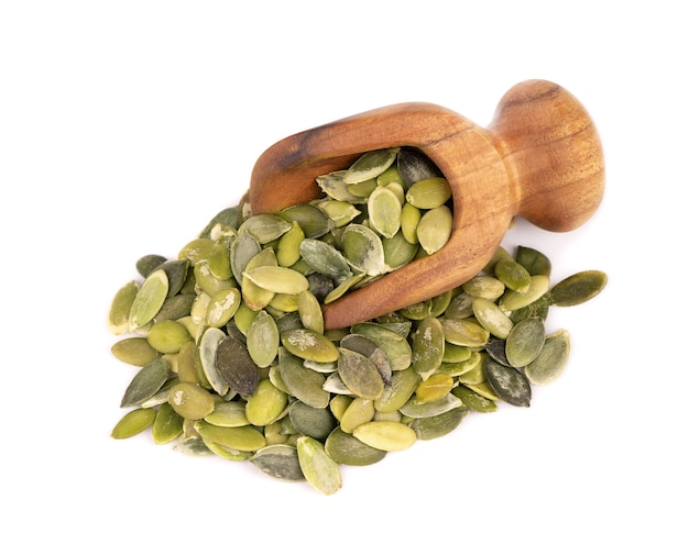 Pumpkin seeds in wooden scoop, isolated on white background.