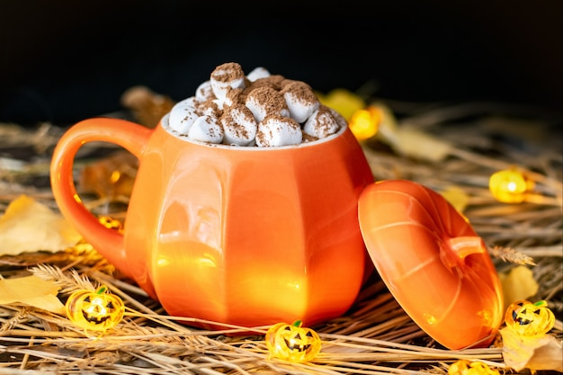 A pumpkin shaped mug with a hot drink, chocolate or cocoa and marshmallows on a table with hay, with a halloween jack-o-lantern garland and dry leaves. autumn still life with warm, cozy home lighting.