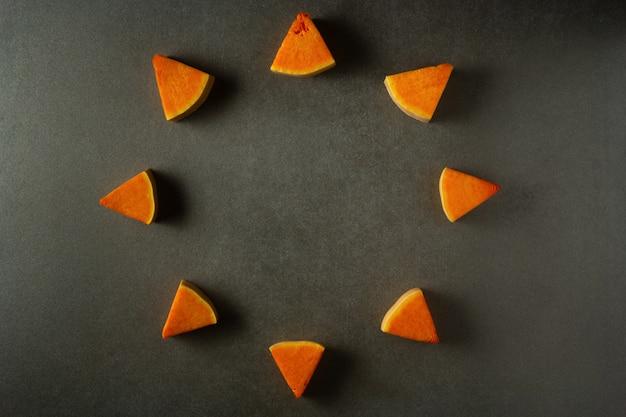 Pumpkin slices round frame on dark grey background