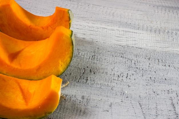 Pumpkin slices on vintage wooden background