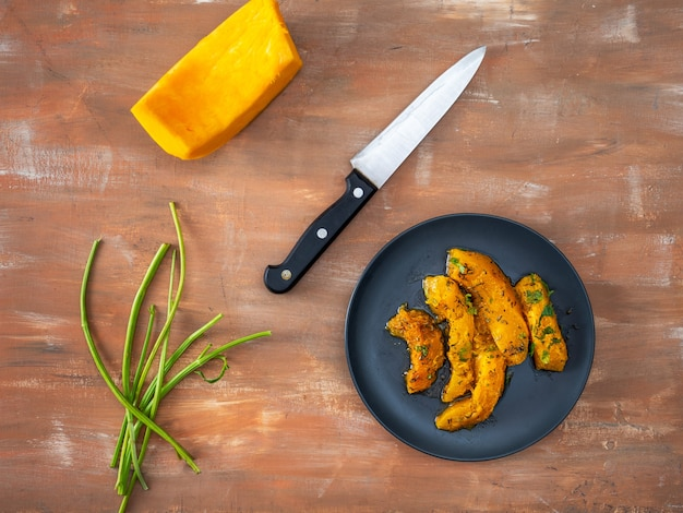 Pumpkin slices with aromatic herbs on a black plate healthy food