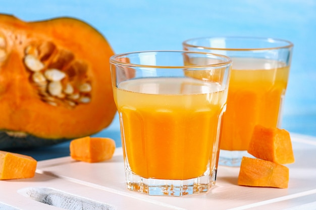 Pumpkin smoothie in glasses. pumpkin juice on a blue table. autumn drinks.