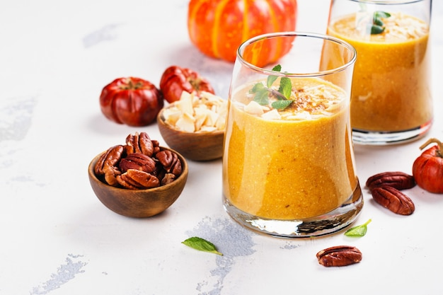Pumpkin smoothie with coconut chips, pecan nuts, cinnamon and mint