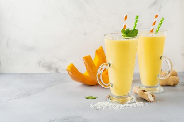 生姜とココナッツの削りくずとミントが入ったカボチャのスムージーを、軽い石またはコンクリートの表面にグラスに入れます。朝食にヘルシーで美味しい飲み物。セレクティブフォーカス。上面図。