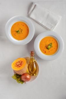 白いテーブルの上のカボチャのスープと有機カボチャ。季節の秋の食べ物-スパイシーなカボチャとニンジンのスープ。上面図。