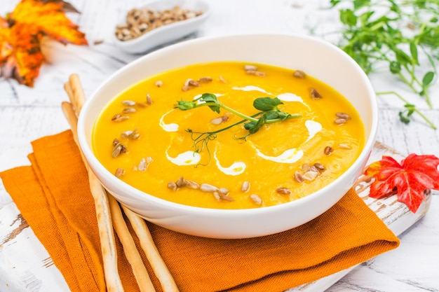 Pumpkin soup on autumn background