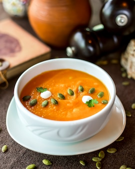 Pumpkin soup in the bowl cream seeds parsley side view
