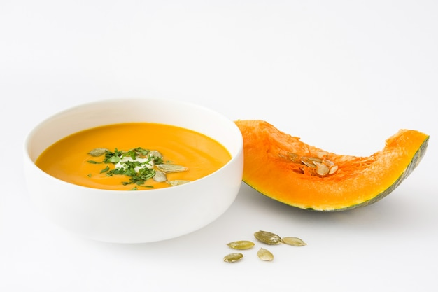 Pumpkin soup in bowl isolated on white