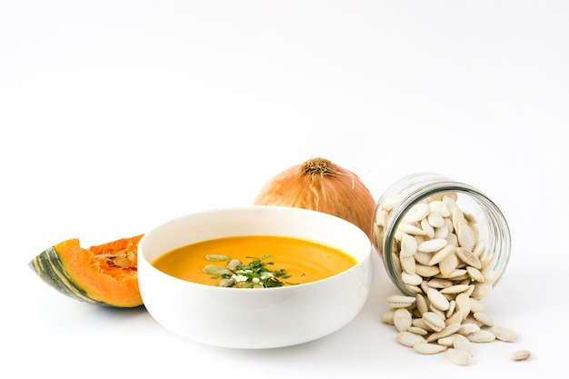 Pumpkin soup in bowl and pumpkin seeds isolated on white
