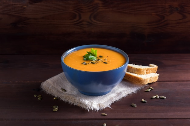 Pumpkin soup in a bowl served with parsley, olive oil and pumpkin seeds