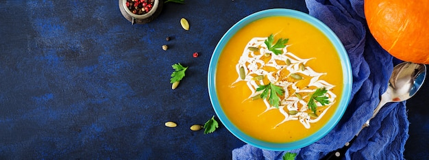 Pumpkin soup in a bowl served with parsley  and pumpkin seeds. vegan soup.  thanksgiving day food.