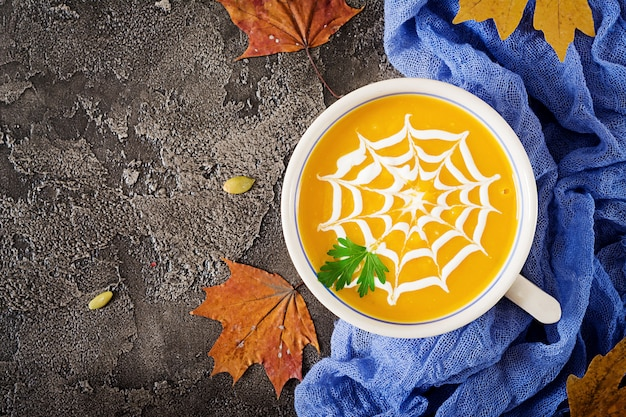 Pumpkin soup in a bowl served with parsley and pumpkin seeds. vegan soup.