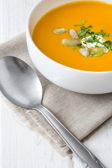 Pumpkin soup in bowl on white wooden table
