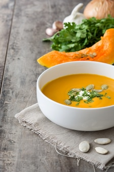 Pumpkin soup in bowl on wooden table