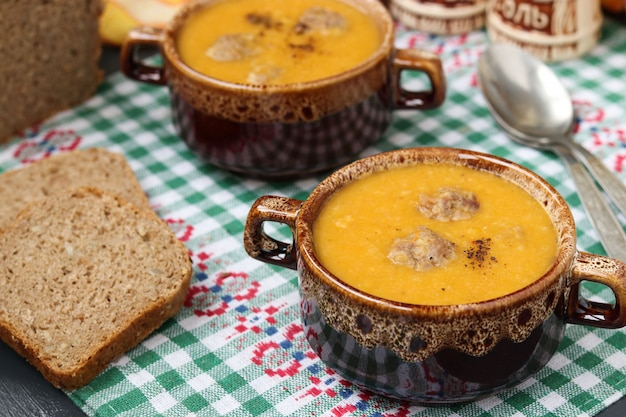 Pumpkin soup in bowls on checkered napkin on a dark .