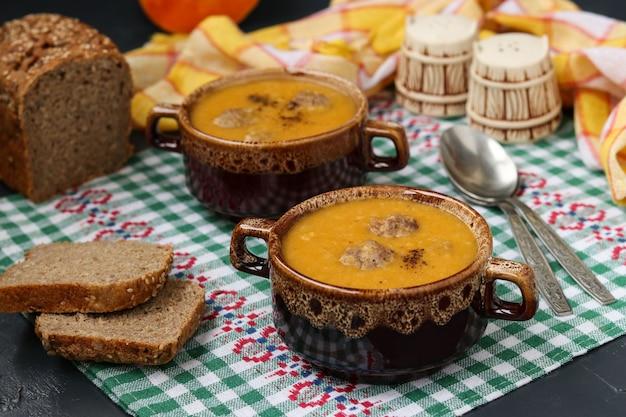 Pumpkin soup in bowls on checkered napkin on dark.