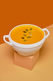 Pumpkin soup decorated pumpkin seeds isolated on orange background. monochrome, minimalism. view from above. copy space.