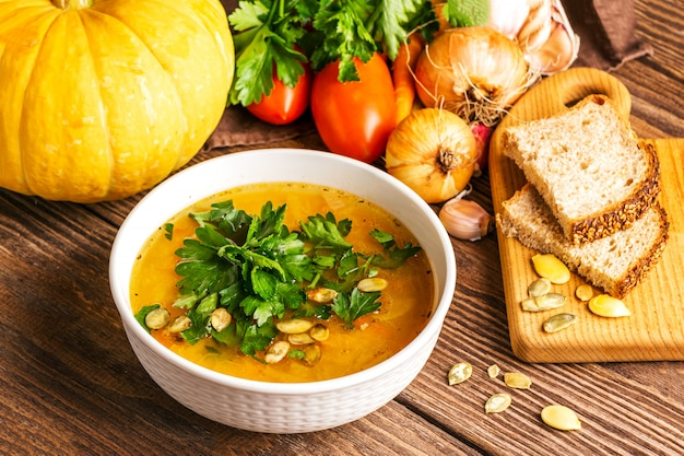 Pumpkin soup and fresh vegetables on wood