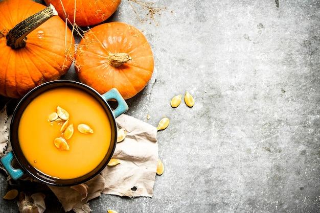 Тыквенный суп из спелой тыквы с семечками на каменном столе