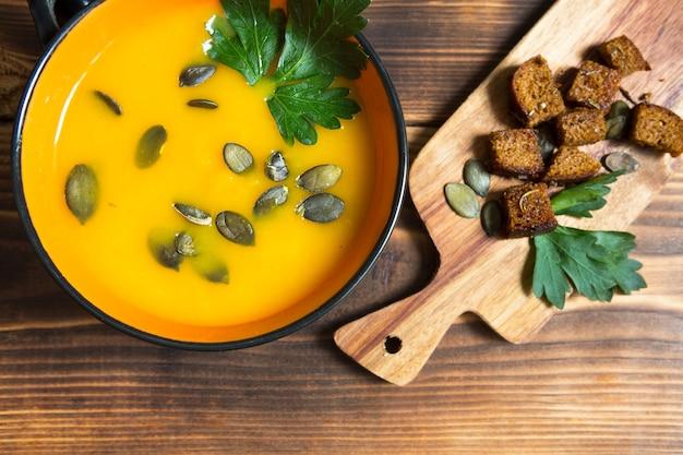 나무 배경에 씨앗과 파슬리가 있는 그릇에 호박 수프. 보드에 향신료와 크래커입니다. 공간을 복사합니다. 추수 감사절, 가을 수프