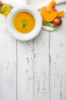 木製のテーブルの上の白いセラミックプレートのカボチャスープ。