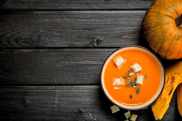 Тыквенный суп в миске с сухарями и целой тыквой. на деревянном фоне