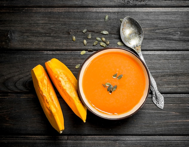 Тыквенный суп в миске с ложкой. на черном деревянном