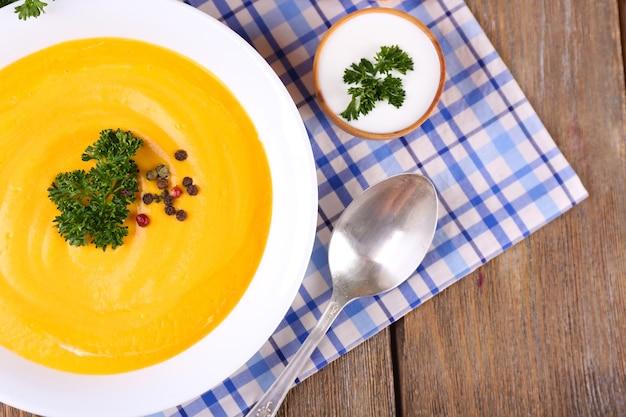 Тыквенный суп в цветной тарелке и кусочек тыквы на салфетке, на деревянном фоне