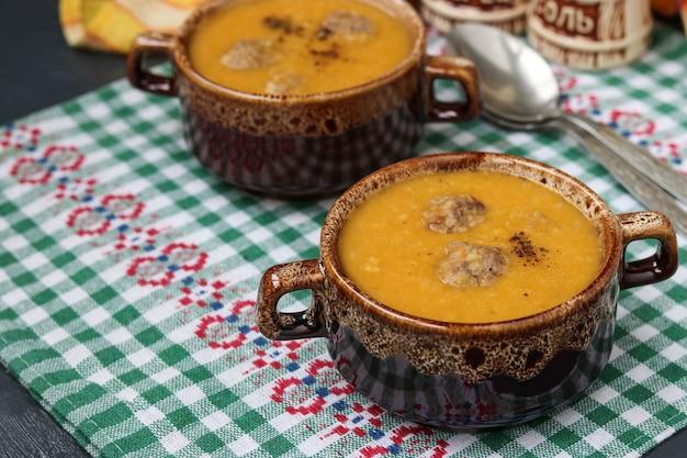 暗いテーブルの上の市松模様のナプキンの2つのボウルのカボチャスープ。