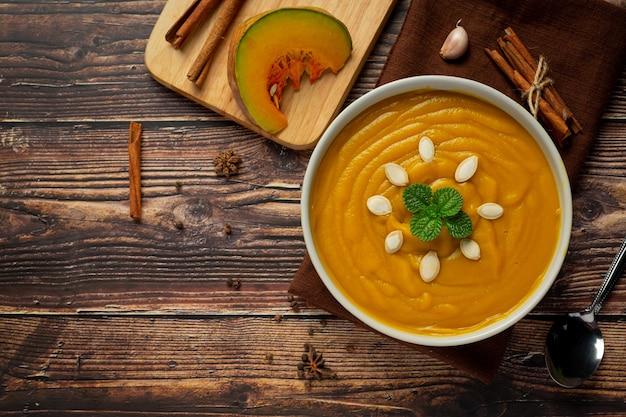 Тыквенный суп в белой миске на деревянном полу