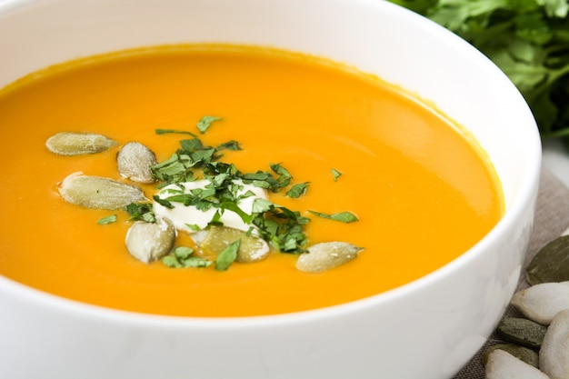 Pumpkin soup and ingredients on white wood
