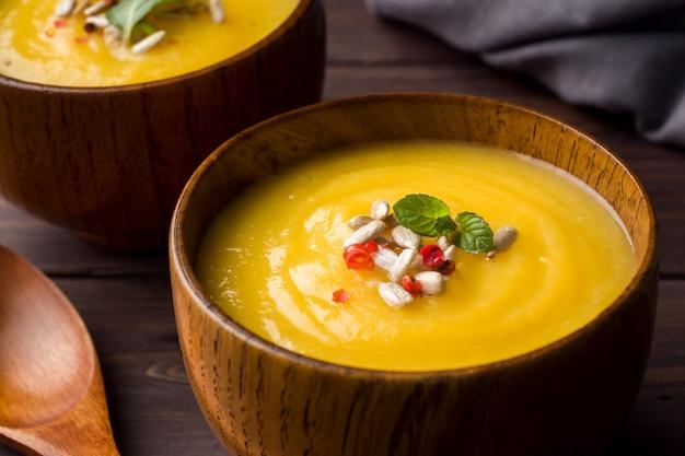 カボチャのスープは、暗いボード上の木製のボウルにスパイスでマッシュポテト。