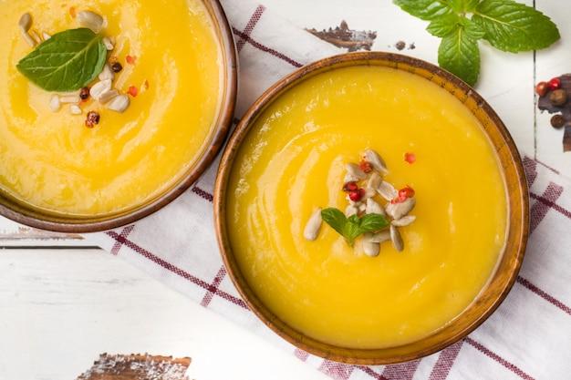 カボチャのスープは、ライトボード上の木製の鉢にスパイスでマッシュポテト。