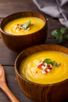 Pumpkin soup mashed with spices in wooden bowls on dark boards.