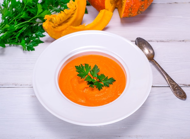 Pumpkin soup puree in a round white plate