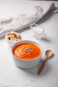 Тыквенный суп-пюре с панировочными сухарями, сливками и семенами на белом фоне.