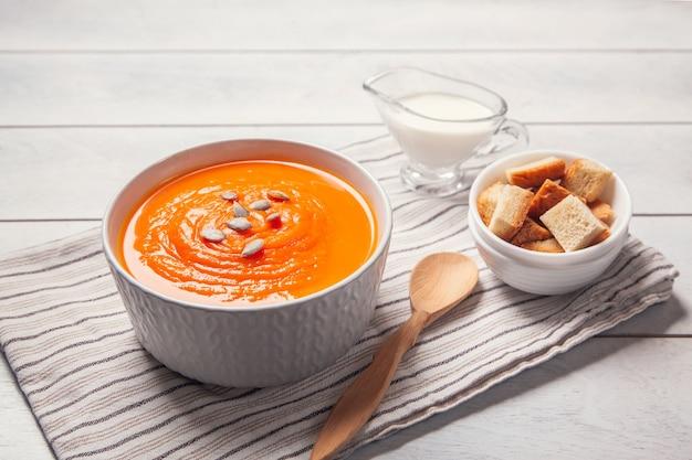 Тыквенный суп-пюре с панировочными сухарями, сливками и семенами на полотенце, белом деревянном фоне.