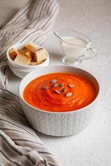 Тыквенный суп-пюре со сливками и семенами на белом фоне.